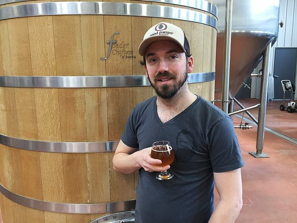 Brewer and co-owner Matt Whalen holds a golden sour ale fermented and aged in this 20-barrel foeder at Good Nature Brewing Co. in Hamilton. (Don Cazentre)
