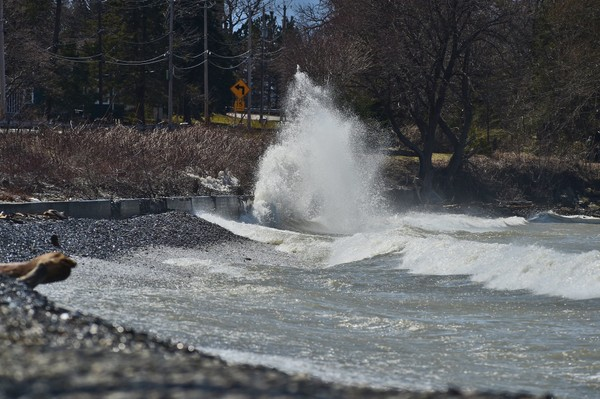 A wave crashes into the shore of Lake Ontario near Rudy's Restaurant outside of Oswego on April 4, 2018.
