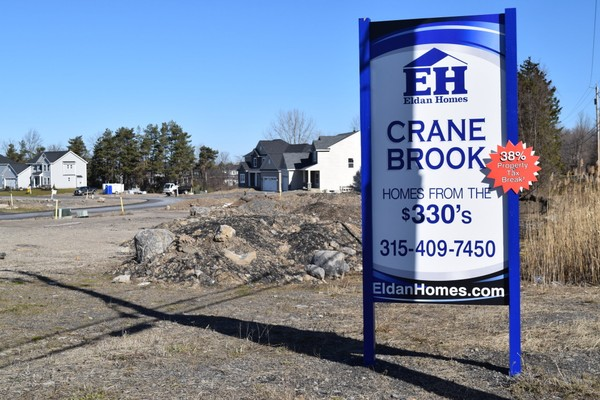 A sign outside a Manlius development advertises a 38 percent tax break on new single-family homes. That's because they are classified as condos, which are assessed at a lower value.(By Michelle Breidenbach)