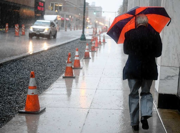 A pedestrian shields himself against the rain in downtown Syracuse in this 2015 file photo. More than an inch of rain could fall Saturday morning.