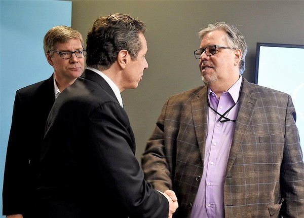 Stephen Cvengros, right, vice president of content for Advance Media New York, and Tim Kennedy, left, president of Advance Media New York, greet Gov. Andrew Cuomo at the company's offices in Syracuse Feb. 4, 2015.