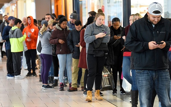Customers check their phones while waiting outside Best Buy at Destiny USA in Syracuse, November 24, 2017. Federal regulators have received a surge in complaints about automated calls to cell phones and land lines.  Michael Greenlar | mgreenlar@syracuse.com