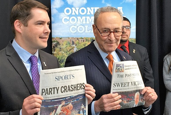 Syracuse Mayor Ben Walsh, left, and U.S. Sen. Charles Schumer hold up copies of The Post-Standard after Syracuse University's win over Michigan State in the 2018 NCAA tournament. Schumer says an import tax on Canadian newsprint threatens Upstate newspapers.