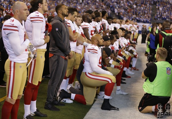 Members of the San Francisco 49ers kneel during the playing of the national anthem before an NFL football game against the Indianapolis Colts, Sunday, Oct. 8, 2017, in Indianapolis. (AP Photo/Michael Conroy)