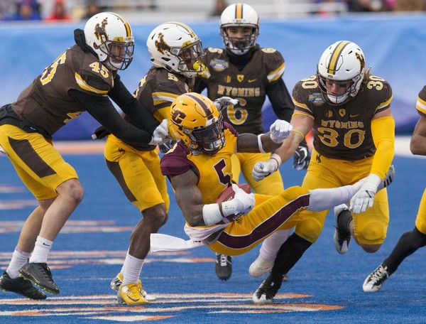 Central Michigan defensive back Devonni Reed (5) gets upended by the Wyoming defense during the Famous Idaho Potato Bowl NCAA college football game in Boise, Idaho, Friday, Dec. 22, 2017. (Darin Oswald/Idaho Statesman via AP)