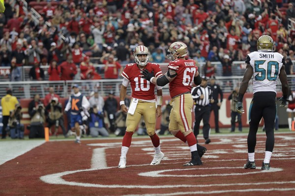 San Francisco 49ers quarterback Jimmy Garoppolo (10) celebrates after scoring a touchdown with center Daniel Kilgore (67) during the first half of an NFL football game against the Jacksonville Jaguars in Santa Clara, Calif., Sunday, Dec. 24, 2017. (AP Photo/Marcio Jose Sanchez)