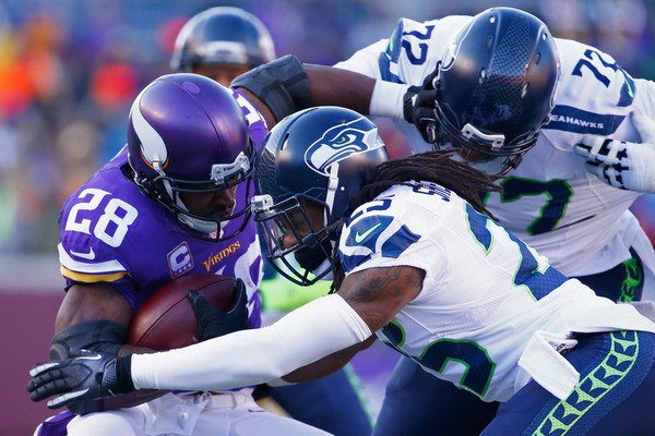 Richard Sherman (25) and Michael Bennett (72) of the Seattle Seahawks attempt to tackle Adrian Peterson (28) of the Minnesota Vikings during the NFC Wild Card Playoff game on Jan. 10, 2016 in Minneapolis, Minnesota. (Jamie Squire/Getty Images)