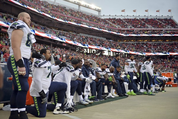 In this Nov. 26, 2017, file photo, Seattle Seahawks players sit and kneel during the playing of the national anthem before an NFL football game against the San Francisco 49ers, in Santa Clara, Calif.
