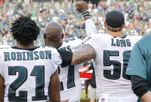 Philadelphia Eagles strong safety Malcolm Jenkins raises his fist with teammate defensive end Chris Long during the national anthem before a preseason game against the Buffalo Bills on Thursday, Aug. 17, 2017, at Lincoln Financial Field in Philadelphia. (Yong Kim | Philadelphia Daily News | TNS)