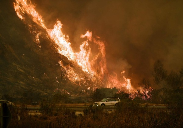 Vehicles pass beside a wall of flames on the 101 highway as it reaches the coast during the Thomas wildfire near Ventura, California on December 6, 2017. California motorists commuted past a blazing inferno Wednesday as wind-whipped wildfires raged across the Los Angeles region, with flames  triggering the closure of a major freeway and mandatory evacuations in an area dotted with mansions. (MARK RALSTONMARK RALSTON/AFP/Getty Images)