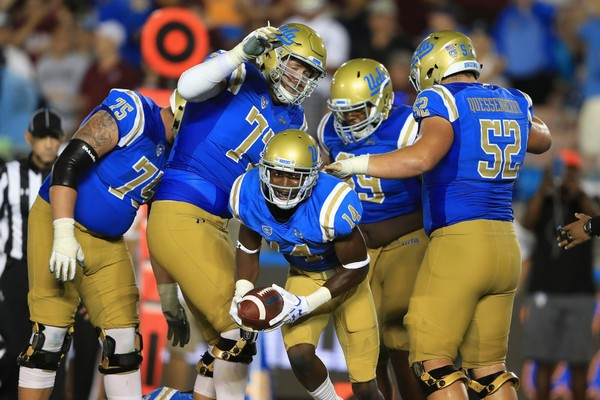 Theo Howard #14 reacts after a touchdown on a pass play as Scott Quessenberry #52, Kolton Miller #77, and Andre James #75 of the UCLA Bruins react during the second half of a game against the Texas A&M Aggies  at the Rose Bowl on September 3, 2017 in Pasadena, California.  (Photo by Sean M. Haffey/Getty Images)