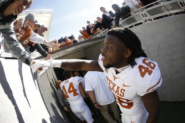 Malik Jefferson #46 of the Texas Longhorns celebrates with a fan following Texas' 38-7 win over the Baylor Bears.