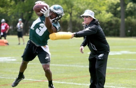 Eagles wide receiver Tim Wilson (13) catches a ball in front of Gunter Brewer, wide receivers coach, during rookie minicamp at the NovaCare Complex in Philadelphia, Friday, May 11, 2018.