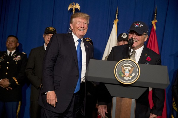 President Donald Trump shares a laugh with Vietnam veteran Steve Hopper of Greenfield, Ill., right, as Trump invites him to speak at a veterans event at the Grand Hyatt, Friday, Nov. 10, 2017, in Danang, Vietnam. Trump is on a five country trip through Asia traveling to Japan, South Korea, China, Vietnam and the Philippines. (AP Photo/Andrew Harnik)