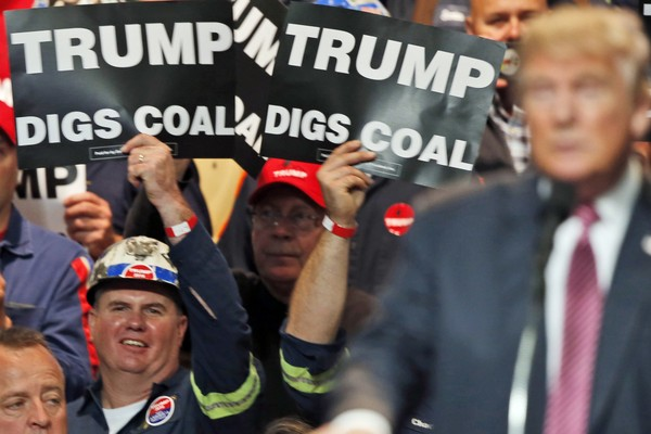 Coal miners wave signs as then-Republican presidential candidate Donald Trump speaks during a rally in Charleston, West Virginia, Thursday, May 5, 2016. (AP Photo/Steve Helber, File)
