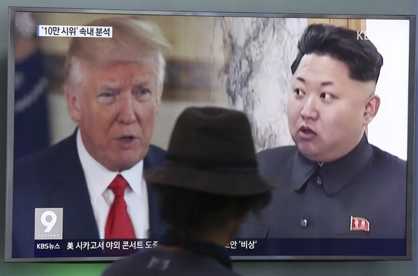 """In this Aug. 10, 2017, file photo, a man watches a television screen showing U.S. President Donald Trump and North Korean leader Kim Jong Un during a news program at the Seoul Train Station in Seoul, South Korea. South Korea's national security director says President Donald Trump has decided he will meet with North Korea's Kim Jong Un """"by May."""" (AP Photo/Ahn Young-joon, File)"""