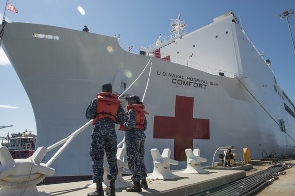 Boatswain's Mate 3rd Class Taryn Armington and Sonar Technician (Surface) Seaman Darian Joseph prepare to cast off mooring lines for the Military Sealift Command hospital ship USNS Comfort (T-AH 20) as the ship departs Naval Station Norfolk to support hurricane relief efforts in Puerto Rico Friday, Sept. 29, 2017 in Norfolk, Va. (MC3 Brittany Tobin/U.S. Navy via AP)