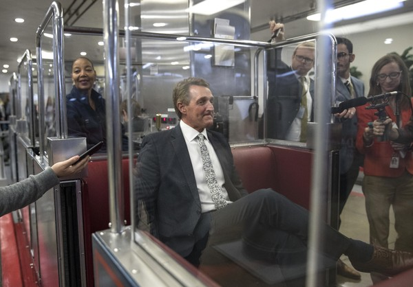 Sen. Jeff Flake, R-Ariz., is flanked by members of the media after he boards the subway on Capitol Hill in Washington, Thursday, Nov. 30, 2017.
