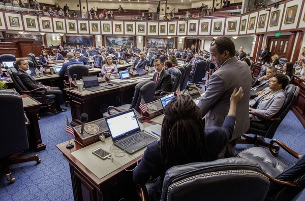 Florida Rep. Patricia Williams (D-Ft. Lauderdale), foreground, pats Rep. Roy Hardemon (D-Miami) on the back aster Hardemon said he got rid of his guns during the school safety debate on the House floor at the Florida Capital in Tallahassee, Fla., Wednesday March 7, 2018.