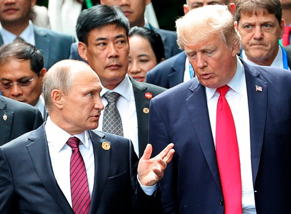 In this Nov. 11, 2017, photo,  President Donald Trump, right, and Russia President Vladimir Putin talk during the family photo session at the APEC Summit in Danang. (Mikhail Klimentyev, Sputnik, Kremlin Pool Photo via AP)
