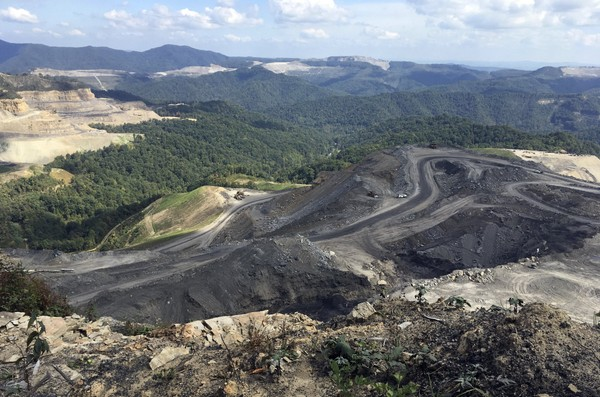 In this Sept. 26, 2017, photo, coal trucks and heavy equipment move on the Middle Ridge surface coal mine, which cut off part of Coal River Mountain in Raleigh County, in southern West Virginia.