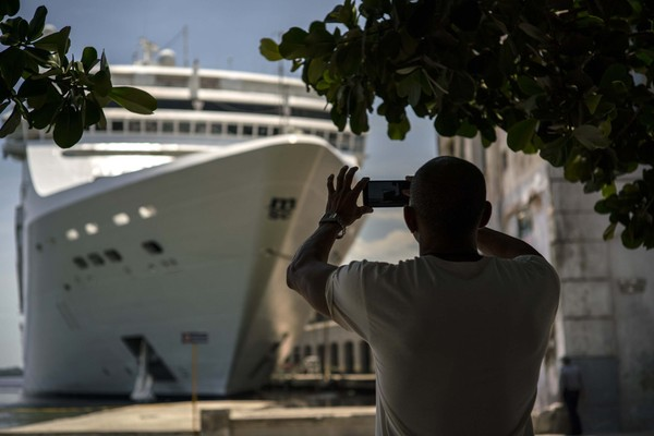 A man takes a photo of a cruise ship in Havana harbor, Cuba, on June 17, 2017.