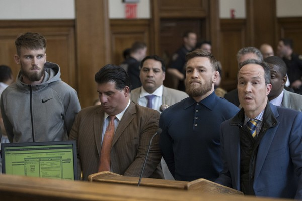 Ultimate fighting stars Conor McGregor, second from right, and Cian Cowley, left, stand with lawyers Jim Walden, right, and John Arlia during an arraignment in Brooklyn Criminal Court, Friday, April 6, 2018 in New York. McGregor is facing criminal charges in the wake of a backstage melee he allegedly instigated that has forced the removal of three fights from UFC's biggest card of the year. (AP Photo/Mary Altaffer, Pool)