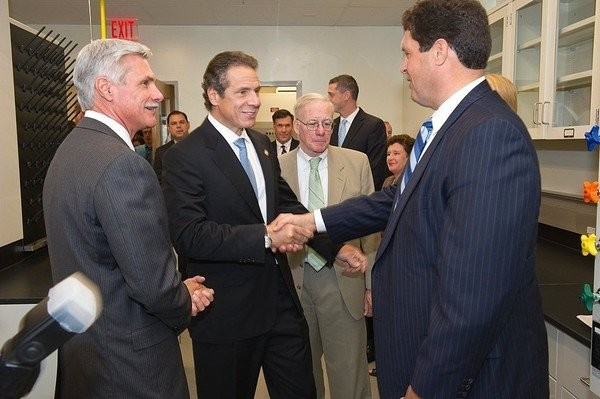 Gov. Andrew Cuomo shakes hands with Steven Aiello of COR Development during an Oct. 2., 2012 visit to the CNY Biotech Accelerator in Syracuse. Behind Cuomo to the right is lobbyist Todd Howe. Former Cuomo aide Joseph Percoco appears behind Cuomo to the left.(Stephen Sartori)