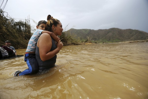 Marlene Ojeda carries her son through a river after a bridge was swept away by Hurricane Maria in Morovis, Puerto Rico.